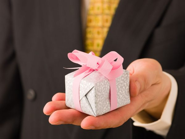 Man on suit give a little gift for somebody